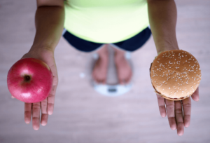 woman on scales with apple in one hand and burger bun in the other