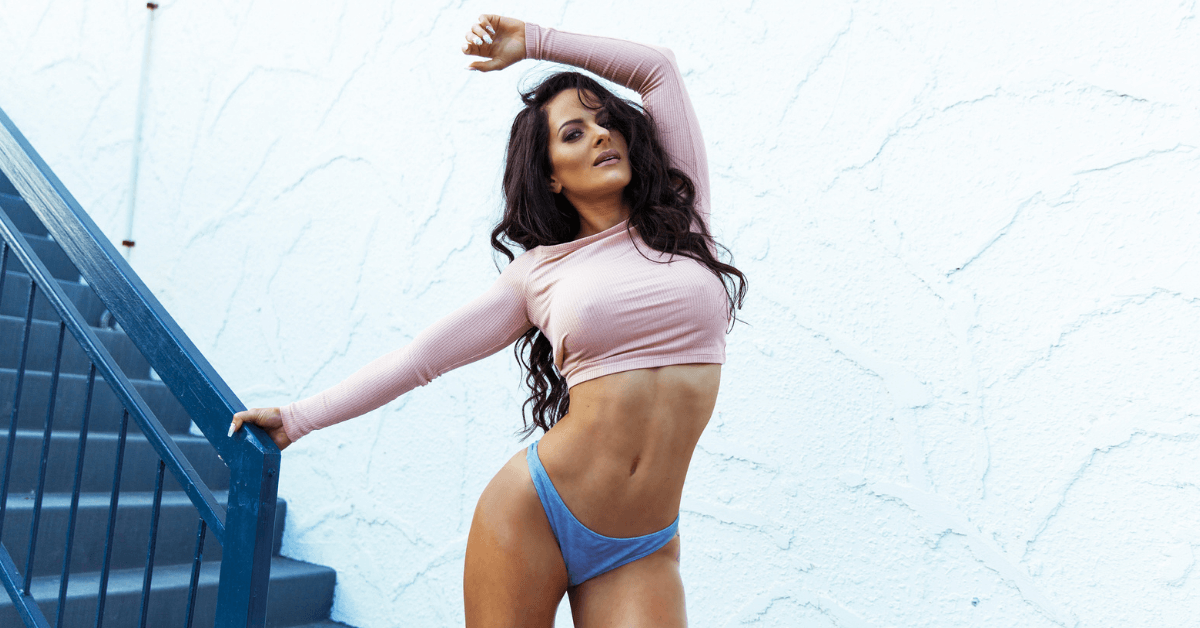 Shelley Darlington posing in front of stairs in a pink top and grey bikini bottoms