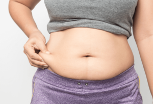 close up of a woman pinching her belly fat